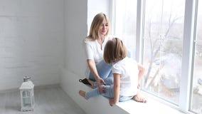 Ευτυχείς mom και κόρη σε ένα φωτεινό στούντιο φιλμ μικρού μήκους