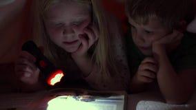 Ευτυχισμένη ζωή με τα κατοικίδια ζώα - μικρά παιδιά που διαβάζουν τη νύχτα ένα βιβλίο κάτω από τις καλύψεις με το μεγάλο σκυλί το φιλμ μικρού μήκους