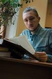 Ευφυές αρσενικό βιβλίο και συνεδρίαση ανάγνωσης σπουδαστών hipster στην επιτραπέζια δημόσια πανεπιστημιακή βιβλιοθήκη Όψη που πυρ στοκ εικόνες με δικαίωμα ελεύθερης χρήσης
