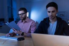 Ευφυής αρσενικός προγραμματιστής που διαβάζει ένα βιβλίο Στοκ Φωτογραφία