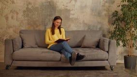 Ευφυής γυναίκα που διαβάζει ένα βιβλίο στον καναπέ απόθεμα βίντεο