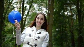 Ευχάριστα γυναίκα που στέκεται και που κυματίζει ένα μπλε μπαλόνι σε ένα ξύλο πεύκων στην slo-Mo απόθεμα βίντεο