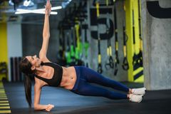 Ευχάριστα η γυναίκα απολαμβάνει τη δευτερεύουσα σανίδα στη γυμναστική στοκ εικόνες