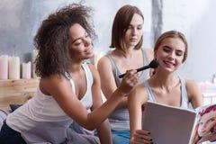 Ευχάριστα νέα κορίτσια που διαβάζουν το περιοδικό στο σπίτι Στοκ Φωτογραφία