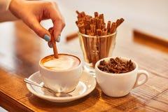 Ευχάριστη γυναίκα που βάζει την κανέλα στο φλιτζάνι του καφέ στοκ εικόνα με δικαίωμα ελεύθερης χρήσης