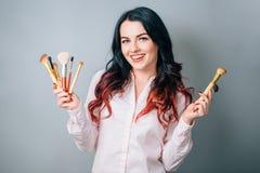 Ευχάριστη γυναίκα που κρατά τρεις βούρτσες makeup και που εξετάζει τη κάμερα Στοκ Εικόνες