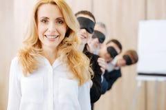 Ευχάριστη ευχαριστημένη γυναίκα που στέκεται μπροστά από τους συναδέλφους της στοκ εικόνα