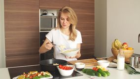 Ευχάριστη νέα γυναίκα που προετοιμάζει το γεύμα σε ένα μαγείρεμα έννοιας κουζινών απόθεμα βίντεο
