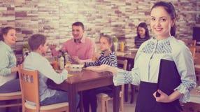 Ευχάριστη νέα σερβιτόρα που καλωσορίζει θερμά τους φιλοξενουμένους στον οικογενειακό καφέ Στοκ Εικόνα