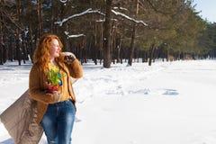 Ευχάριστη σγουρή μαλλιαρή γυναίκα που εξετάζει την απόσταση με το παλτό της πέρα από τον ώμο και το χειμερινό δάσος στο υπόβαθρο στοκ φωτογραφία με δικαίωμα ελεύθερης χρήσης
