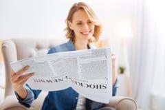 Ευχάριστη χαριτωμένη γυναίκα που χαμογελά διαβάζοντας τις αστείες ειδήσεις σε μια τοπική εφημερίδα Στοκ φωτογραφία με δικαίωμα ελεύθερης χρήσης
