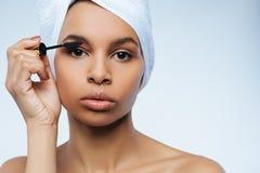 Ευχάριστη χαριτωμένη γυναίκα που χρησιμοποιεί mascara στοκ εικόνες