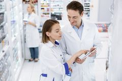 Ευχάριστοι δύο φαρμακοποιοί που ελέγχουν την παρουσία στοκ εικόνα