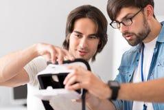 Ευχάριστοι συνάδελφοι που εξετάζουν τη συσκευή εικονικής πραγματικότητας Στοκ Φωτογραφία