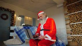 Ευχάριστος Άγιος Βασίλης που εργάζεται στο lap-top απόθεμα βίντεο