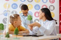 Ευχάριστος δάσκαλος που ακούει την απάντηση σπουδαστών για τη φωτοσύνθεση Στοκ Εικόνα