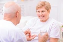 Ευχάριστος ενήλικος σύζυγος που δίνει τα χάπια στη σύζυγό του Στοκ Εικόνες