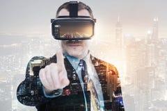 Ευχάριστος επιχειρηματίας που φορά την κάσκα VR και που δείχνει στη κάμερα Στοκ Εικόνες