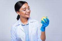Ευχάριστος εργαζόμενος εργαστηρίων που εξετάζει το μήλο στα χέρια της Στοκ Εικόνες