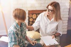 Ευχάριστος θηλυκός ψυχολόγος που μιλά με ένα σχολικό αγόρι Στοκ Εικόνες