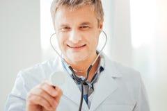 Ευχάριστος ικανοποιημένος γιατρός που χρησιμοποιεί το statoscope και το χαμόγελό του Στοκ εικόνα με δικαίωμα ελεύθερης χρήσης