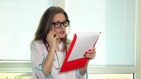 Ευχάριστος καλός θηλυκός γιατρός που έχει τη συνομιλία με τον ασθενή στο κινητό τηλέφωνο απόθεμα βίντεο