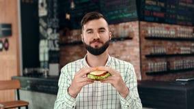 Ευχάριστος μοντέρνος νεαρός άνδρας hipster που δαγκώνει juicy ορεκτικό burger που απολαμβάνει το γούστο που εξετάζει τη κάμερα φιλμ μικρού μήκους