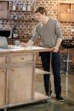 Ευχάριστος νεαρός άνδρας που προσέχει το τηλεοπτικό σεμινάριο στο lap-top Στοκ Εικόνες