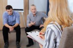 Ευχάριστος πεπειραμένος ψυχολόγος που παίρνει τις σημειώσεις Στοκ Εικόνα