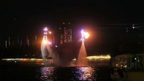 Ευχάριστος φλογερός ένας ελαφρύς παρουσιάζει στα flyboards στην πόλη νύχτας στο νερό απόθεμα βίντεο