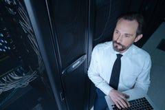 Ευχάριστος όμορφος τεχνικός που εργάζεται στο δωμάτιο κεντρικών υπολογιστών Στοκ Εικόνα
