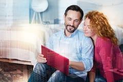 Ευχάριστο άτομο που παρουσιάζει αποτελέσματα της εργασίας του στη σύζυγό του Στοκ φωτογραφία με δικαίωμα ελεύθερης χρήσης