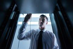 Ευχάριστο άτομο της Νίκαιας που βάζει το καλώδιο Ethernet στον κεντρικό υπολογιστή ραφιών Στοκ Φωτογραφίες