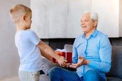 Ευχάριστο αγόρι της Νίκαιας που δίνει ένα παρόν στον παππού του Στοκ Εικόνες
