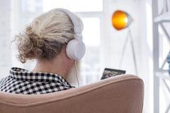 Ευχάριστο ανώτερο άτομο που κοιτάζει μέσω του playlist του Στοκ φωτογραφία με δικαίωμα ελεύθερης χρήσης