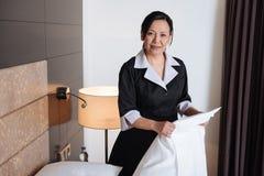Ευχάριστο ασιατικό κορίτσι ξενοδοχείων που κρατά ένα φύλλο στοκ εικόνες