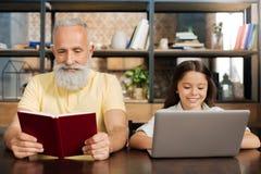 Ευχάριστο βιβλίο ανάγνωσης παππούδων ενώ η εγγονή του που χρησιμοποιεί το lap-top στοκ φωτογραφία