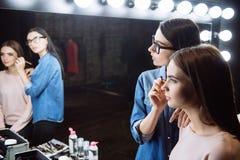 Ευχάριστο επαγγελματικό visagiste που εξετάζει τον καθρέφτη Στοκ εικόνα με δικαίωμα ελεύθερης χρήσης