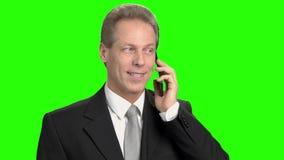 Ευχάριστο εύθυμο επιχειρησιακό άτομο που μιλά στο τηλέφωνο απόθεμα βίντεο
