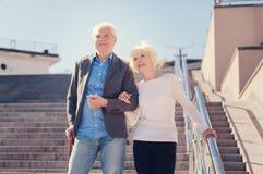 Ευχάριστο ηλικιωμένο ζεύγος που πηγαίνει κάτω από το αγκαζέ σκαλοπατιών στοκ εικόνα