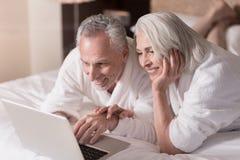 Ευχάριστο ηλικίας ζεύγος που κάνει σερφ το Διαδίκτυο στο σπίτι Στοκ φωτογραφία με δικαίωμα ελεύθερης χρήσης