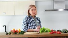 Ευχάριστο νέο θηλυκό που τρώει τα φρέσκα οργανικά λαχανικά κατά τη διάρκεια της μαγειρεύοντας σαλάτας στο μέσο πυροβολισμό κουζιν απόθεμα βίντεο
