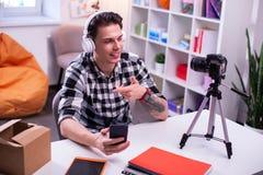 Ευχάριστο σκοτεινός-μαλλιαρό άτομο που φορά τα άσπρα ακουστικά και που συνδέει τα με το smartphone στοκ φωτογραφία