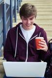 Ευχάριστο φλιτζάνι του καφέ εκμετάλλευσης ατόμων και να κουβεντιάσει στο lap-top Στοκ Εικόνες
