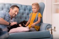 Ευχάριστο όμορφο άτομο που κρατά μια γάτα Στοκ φωτογραφία με δικαίωμα ελεύθερης χρήσης