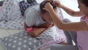 Ευχάριστο preschoolgirl που κάνει ένα hairstyle για τον πατέρα της φιλμ μικρού μήκους