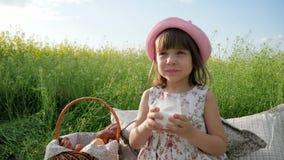 Ευχαρίστηση στο πρόσωπο παιδιών ` s, γάλα που διαφημίζει, υγιή τρόφιμα για τα παιδιά, λίγο κορίτσι στα ποτά πικ-νίκ, γαλακτοκομεί απόθεμα βίντεο