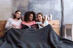 Ευχαριστημένα χαμογελώντας κορίτσια που διαβάζουν το περιοδικό στο κρεβάτι Στοκ Εικόνες