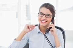 Ευχαριστημένη αριστοκρατική καφετιά μαλλιαρή επιχειρηματίας που απαντά στο τηλέφωνο Στοκ Εικόνα