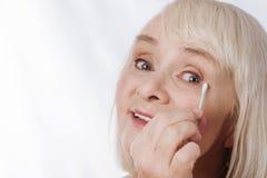 Ευχαριστημένη γκρίζα μαλλιαρή γυναίκα που χρησιμοποιεί μια πατσαβούρα βαμβακιού στοκ εικόνα